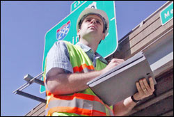 man in hard hat working outside with clip board