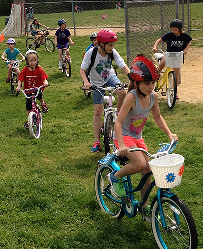 Antietam Elementary School students ride their bicycles across the school's fields.
