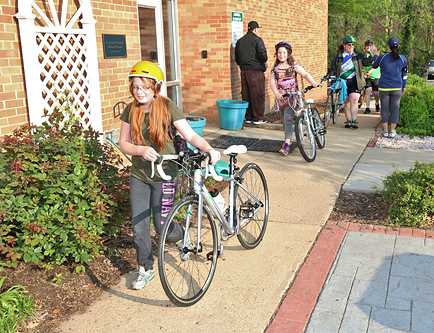 Students at Campbell Elementary School walk their bikes on campus.